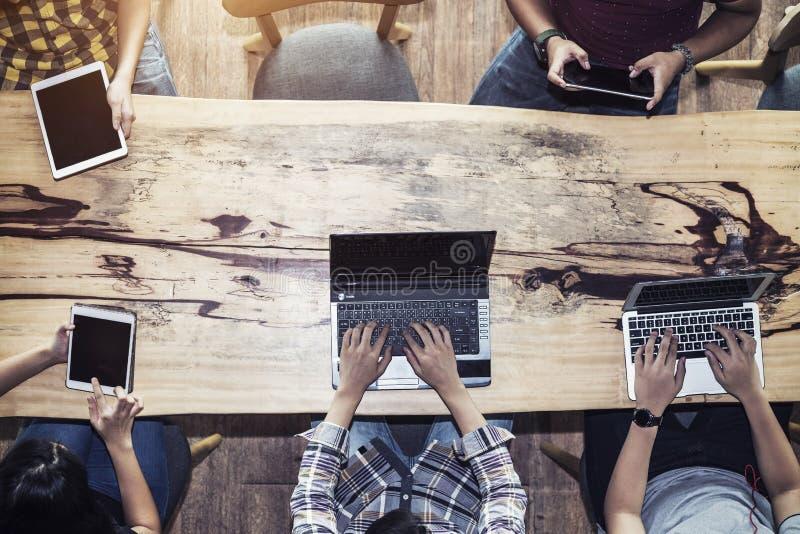 Povos que usam o dispositivo ao trabalho na tabela Tecnologia da conexão de rede foto de stock royalty free