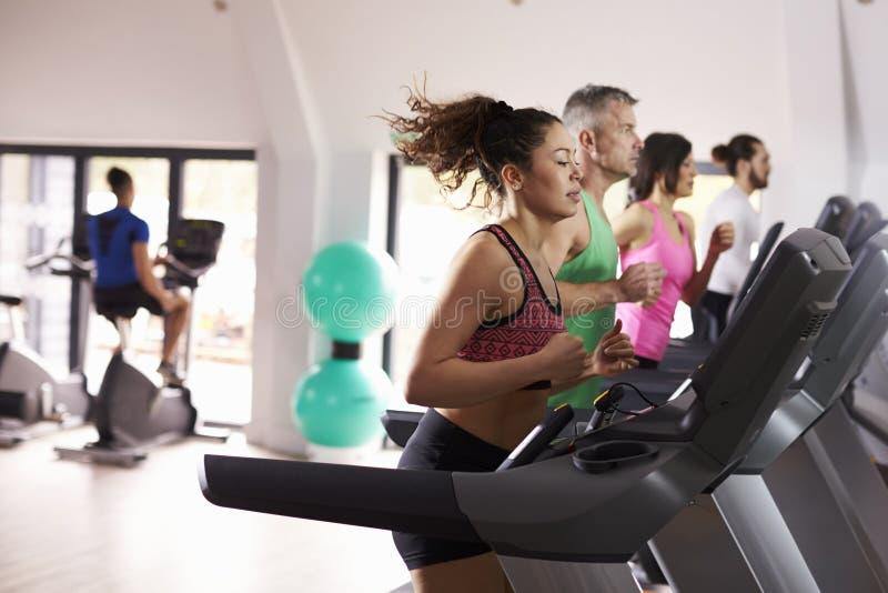 Povos que usam o equipamento no Gym ocupado imagem de stock royalty free