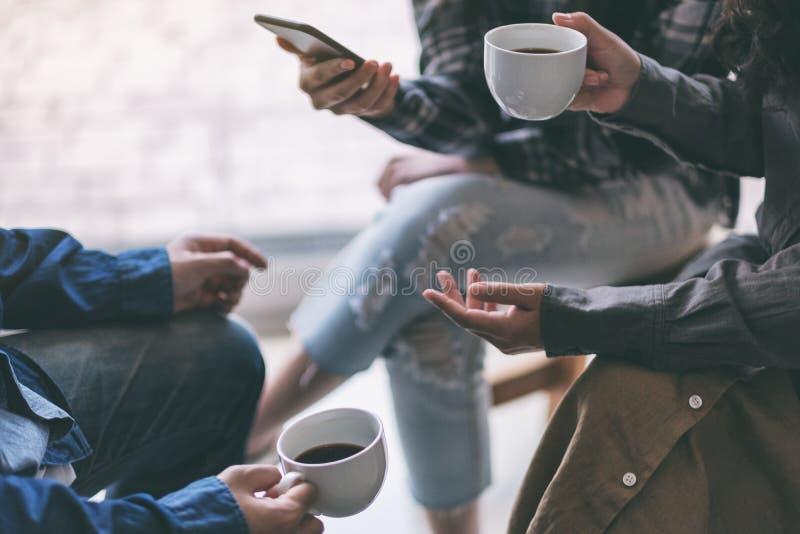 Povos que usam o telefone e bebendo o café junto imagens de stock royalty free