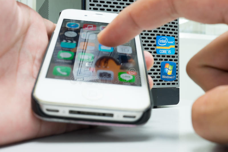 Povos que usam o telefone esperto em vez do computador fotografia de stock