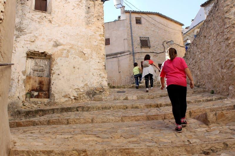 Povos que vão acima ao longo de uma rua de pedra em cima em uma rua histórica de Bocairent, Valência, Espanha fotos de stock royalty free
