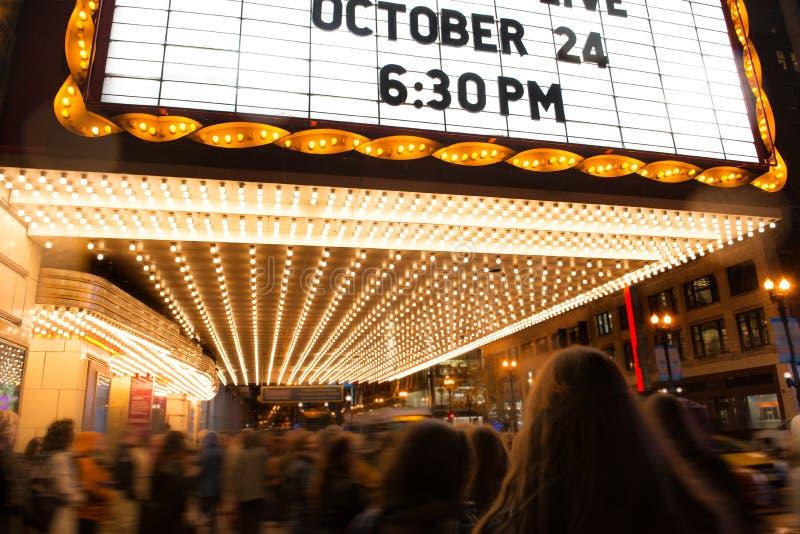 Povos que vão ao teatro do cinema no tempo da noite foto de stock royalty free