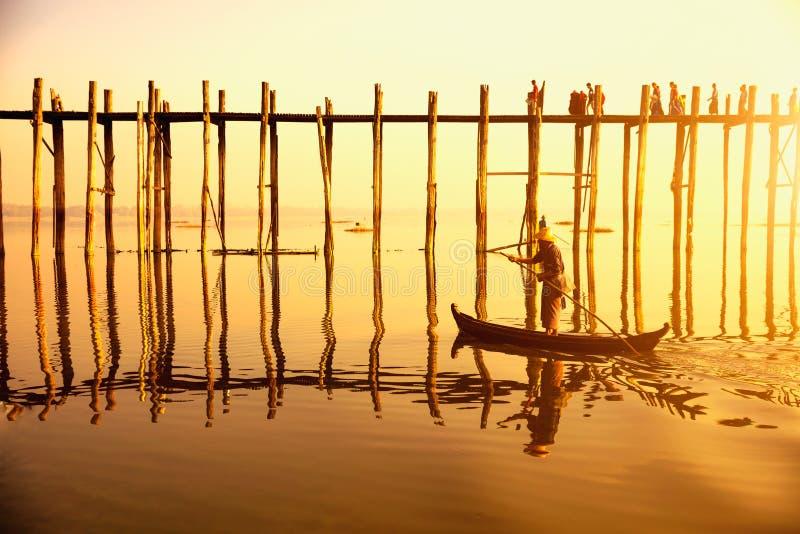 Povos que viajam através da ponte de U Bein na noite Mandal fotografia de stock