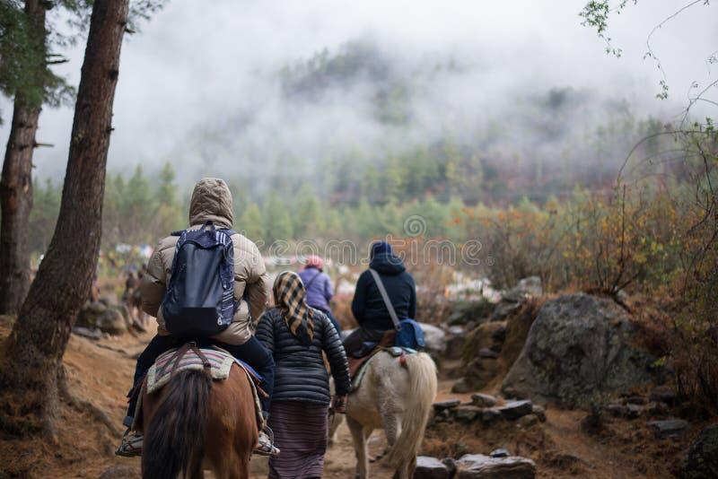 Povos que viajam a Taktshang Goemba pelo cavalo foto de stock