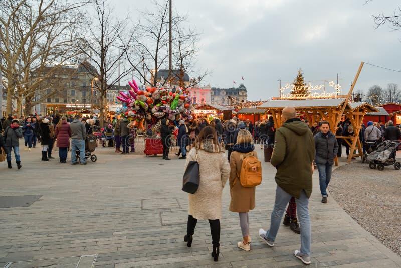 Povos que visitam o mercado tradicional do Natal perto de Bellevue em Zurique foto de stock