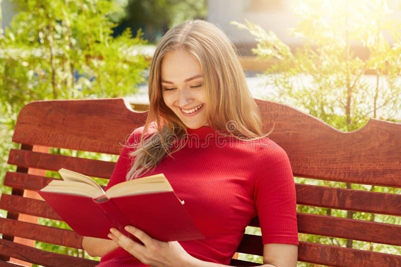 Povos, resto, passatempo, conceito das férias Mulher louro alegre na camiseta vermelha que guarda suas estórias boas de leitura d fotos de stock royalty free