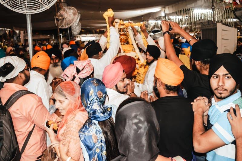 Povos sikh que tentam tocar no ídolo do holi quando foi tomado fora dos locais do templo para imagens de stock royalty free