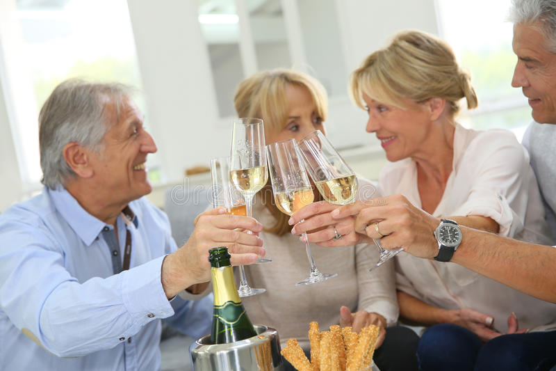 Povos superiores felizes que comemoram com champanhe imagens de stock royalty free