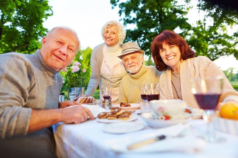 Povos superiores felizes que sentam-se na tabela do grupo no jardim imagens de stock royalty free