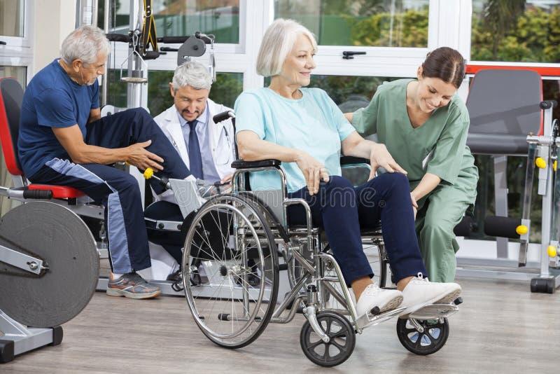 Povos superiores que estão sendo ajudados por fisioterapeuta no centro de reabilitação fotografia de stock