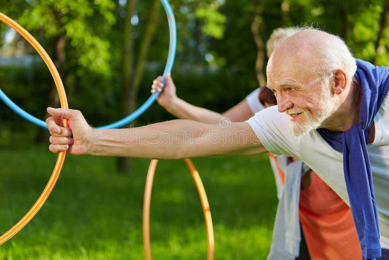 Povos superiores que fazem esportes com as aros no jardim imagens de stock royalty free
