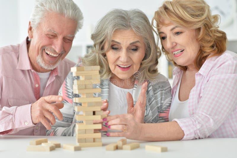 Povos superiores que jogam com blocos de madeira foto de stock