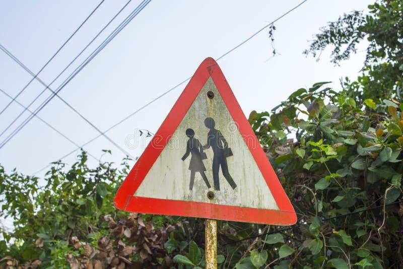 Povos triangulares do cuidado do sinal de estrada em um fundo de arbustos verdes foto de stock