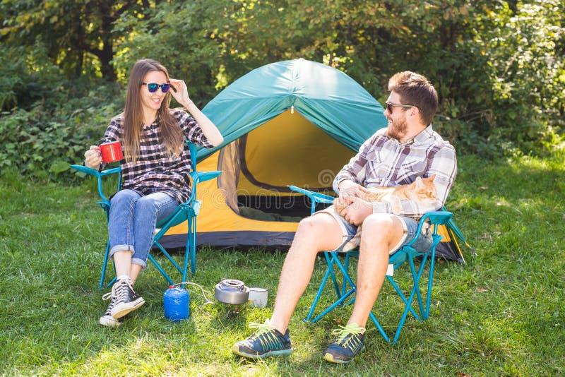 Povos, turismo do verão e conceito da natureza - pares novos que sentam-se perto de uma barraca foto de stock royalty free