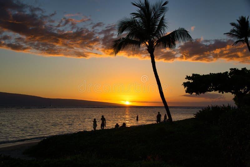 Povos Unidentifiable que andam no sunsetwith uma vista de Lanai da praia do bebê na ilha de Maui fotografia de stock royalty free