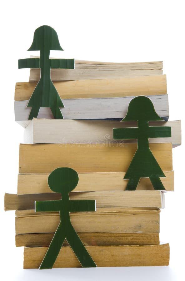Povos verdes em uma pilha dos livros imagens de stock