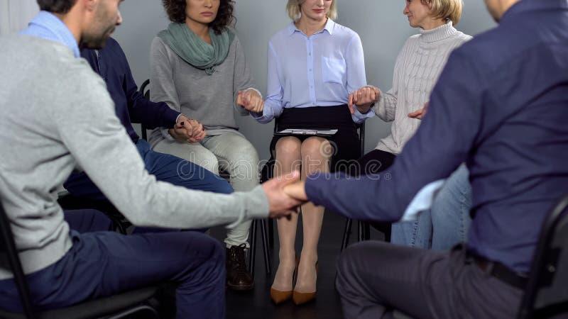 Povos viciado que sentam-se no círculo e que guardam as mãos na sessão de terapia, apoio imagens de stock royalty free