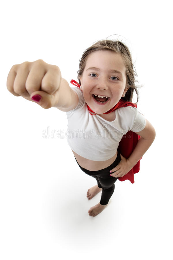 Pow! super girl!. Pretty young girl posing with her right arm in the air ready to fly royalty free stock photos