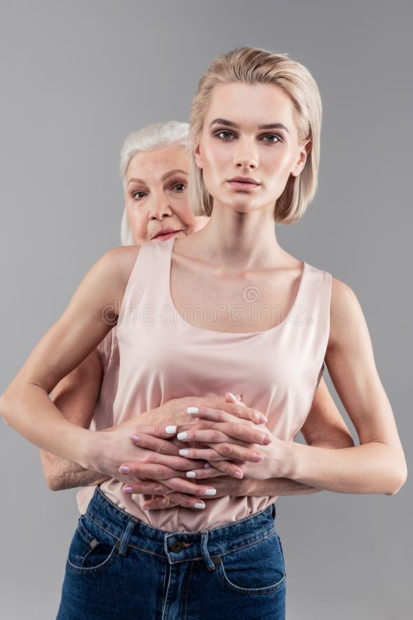 Poważny blondynki dziewczyny palce z jej senior matką i ręk skrzyżowanie obraz stock