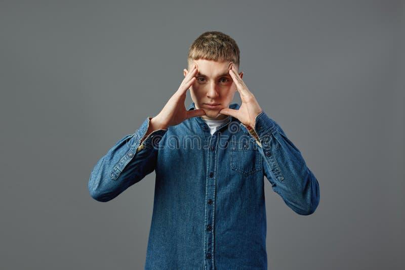 Poważny facet ubierał w cajg koszulowej pozycji z jego rękami na jego twarzy w studiu na szarym tle zdjęcia royalty free