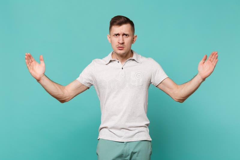Poważny młody człowiek gestykuluje w przypadkowych ubraniach demonstrujący rozmiar z horyzontalnym workspace odizolowywającym na  zdjęcie stock