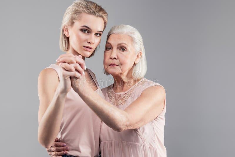 Poważny siwowłosy macierzysty przytulenie jej córka podczas gdy one stoi obrazy stock
