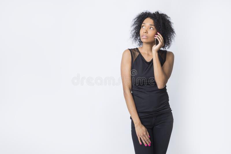 Poważna amerykanin afrykańskiego pochodzenia kobieta opowiada na jej telefonie zdjęcia stock