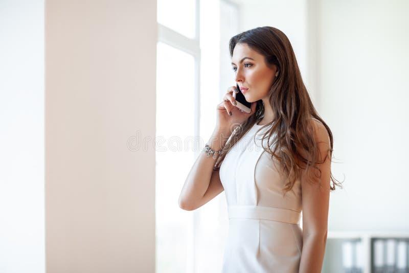 Poważna biznesowa kobieta opowiada na smartphone w biurze zdjęcie royalty free