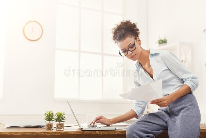 Poważna biznesowa kobieta pracuje na laptopie przy biurem zdjęcie stock