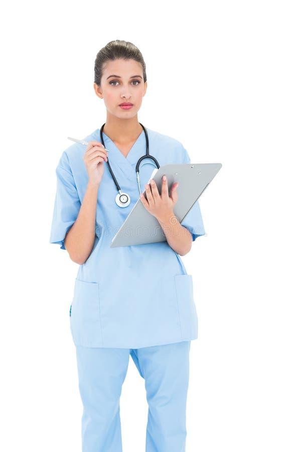 Poważna brown z włosami pielęgniarka w błękicie szoruje sprawdzać raport zdjęcie royalty free