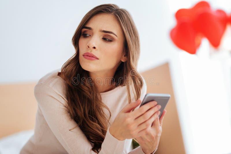 Poważna dama myśleć o coś podczas gdy używać telefon obrazy royalty free