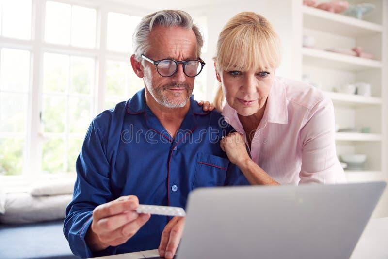 Poważna, Dojrzała Para W Domu, Wyszukująca Informacje O Lekach Online Za Pomocą Notebooka fotografia royalty free