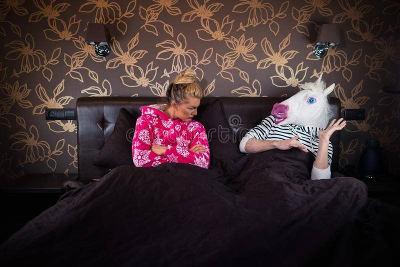 Poważna dziewczyna w piżamie siedzi na łóżku z chłopakiem obraz stock