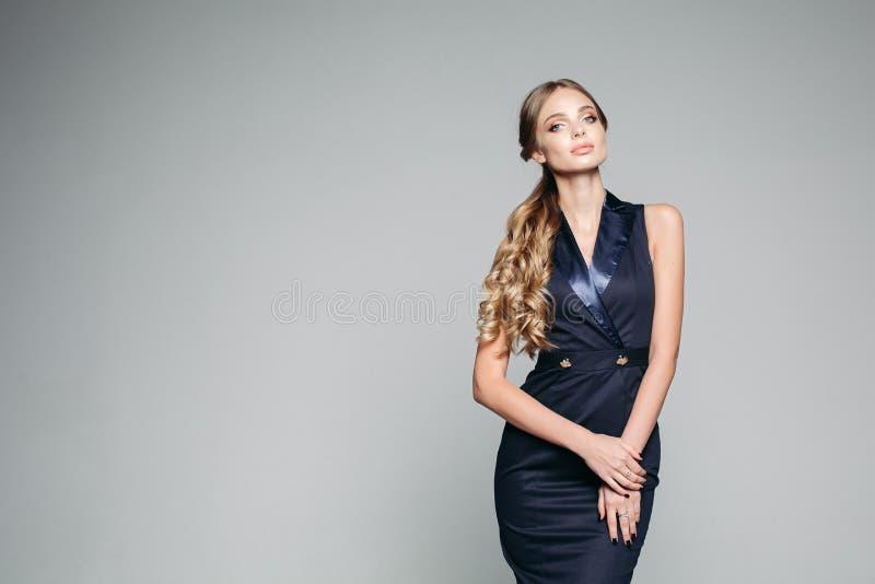 Poważna i uwodzicielska kobieta jest ubranym w eleganckim zmroku - błękit suknia zdjęcie royalty free