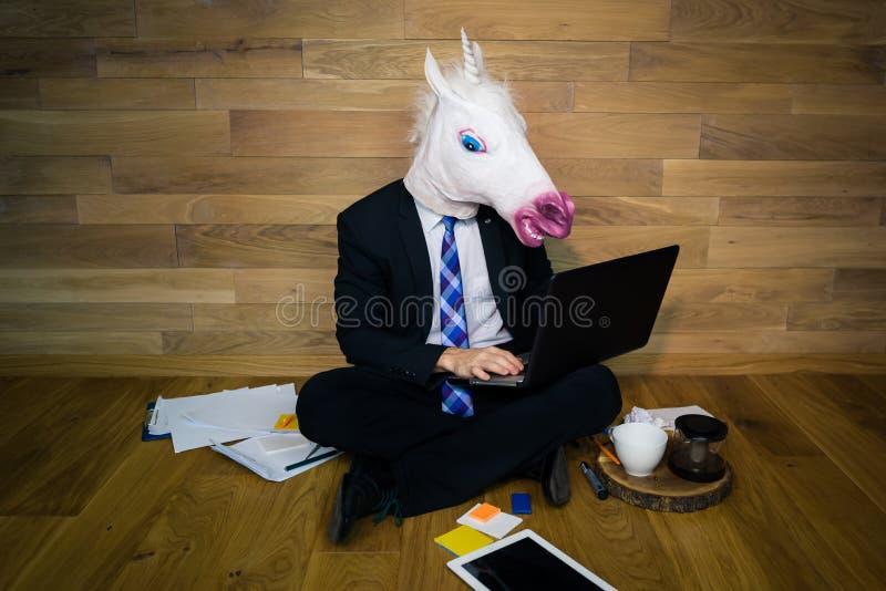Poważna jednorożec w krawacie i kostiumu pracuje w domu biuro z gadżetami zdjęcie royalty free
