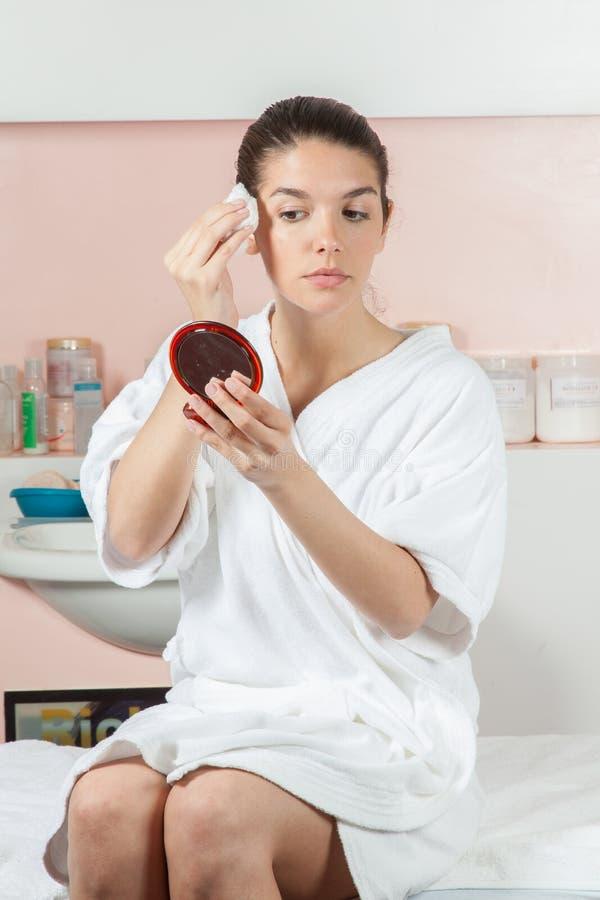 Poważna kobieta czyści jej twarz z bawełną obrazy royalty free