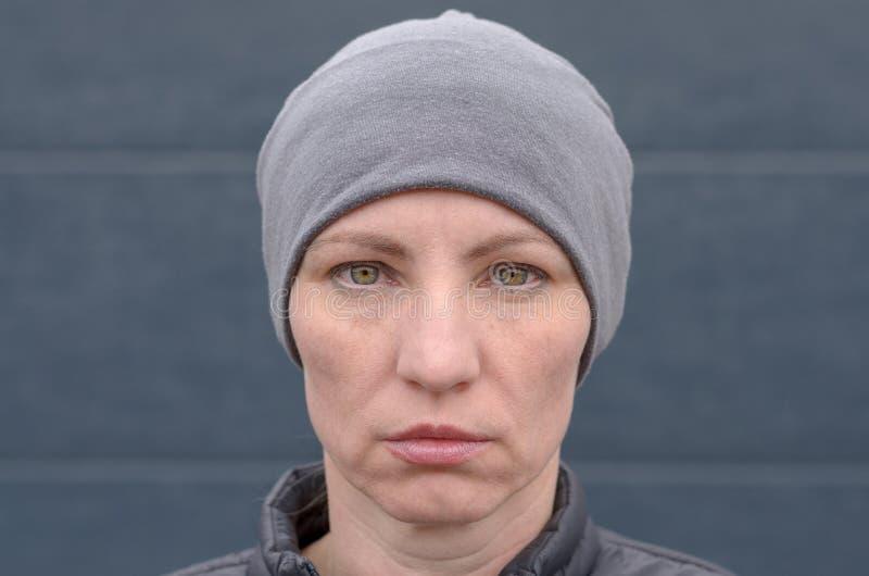 Poważna kobieta jest ubranym szarego beanie kapelusz fotografia stock