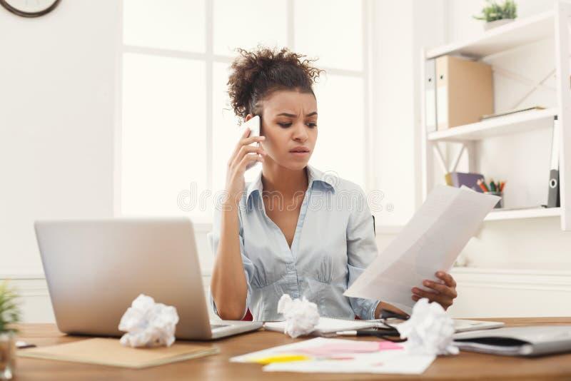 Poważna kobieta konsultuje telefonem przy biurem obraz royalty free