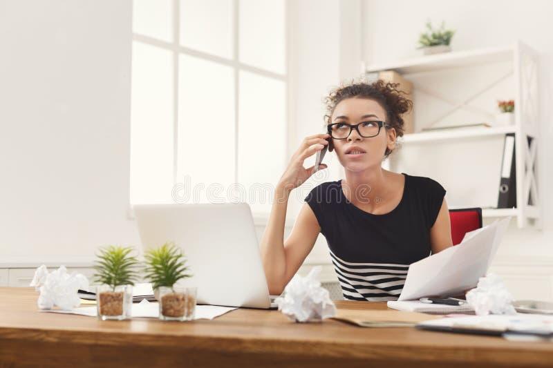 Poważna kobieta konsultuje telefonem przy biurem fotografia stock