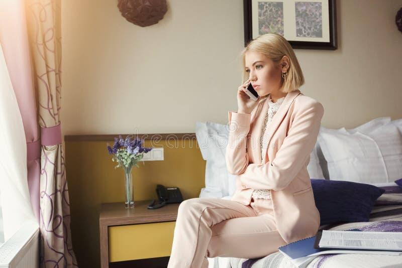 Poważna kobieta opowiada na telefonie w pokoju hotelowym zdjęcie royalty free