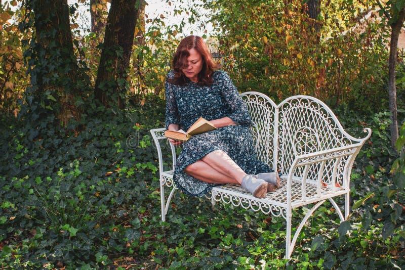 Poważna kobieta 50 rok w retro stylu czyta książkę w romantycznym ogródzie z białą dekoracyjną antykwarską ławką obraz royalty free