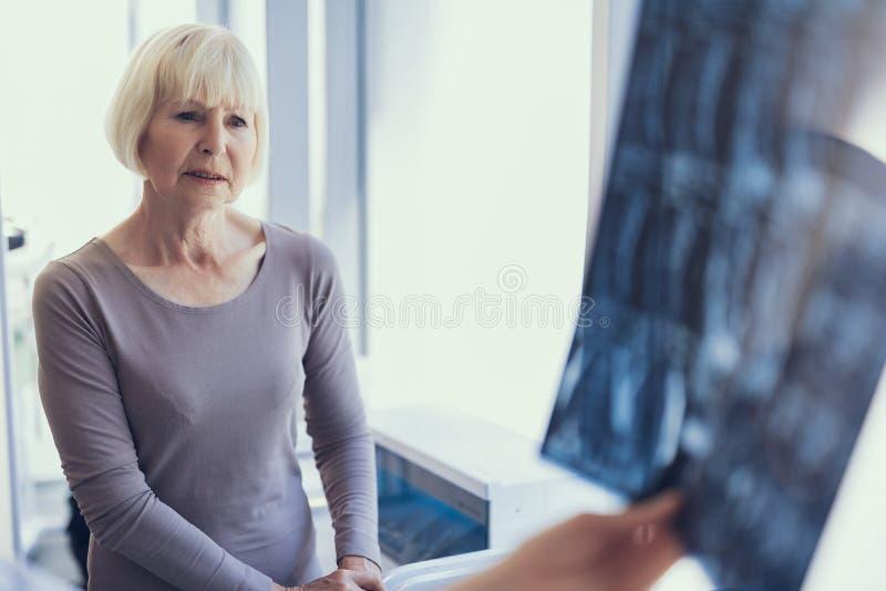 Poważna kobieta słucha Radiologiczna analiza zdjęcie royalty free