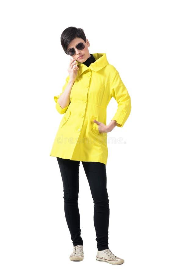 Poważna krótkiego włosy kobieta opowiada na telefonie patrzeje puszek w żółtym żakiecie zdjęcia stock