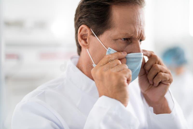 Poważna lekarka marszczy brwi daleko ochronną maskę i bierze zdjęcia stock