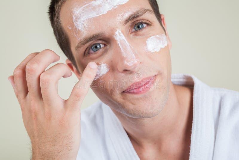 Poważna mężczyzna kładzenia twarzy śmietanka z twój palcem obraz royalty free