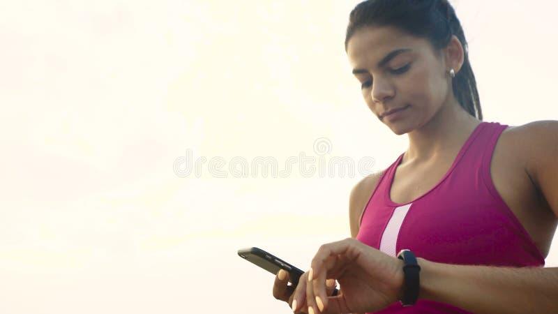 Poważna młoda aktywna kobieta sprawdza mily na jej działającym zegarku fotografia stock