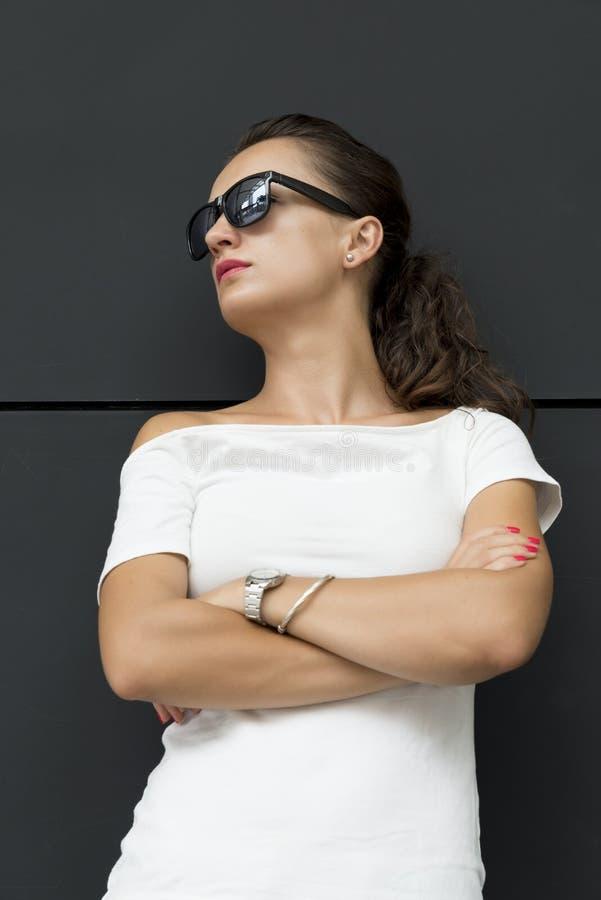 Poważna młoda brunetki kobieta z rękami krzyżować fotografia royalty free