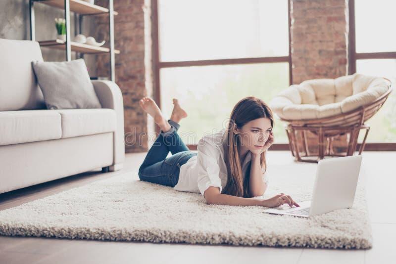 Poważna młoda dama kłama na wygodnym dywanie w livi studiuje, zdjęcia royalty free