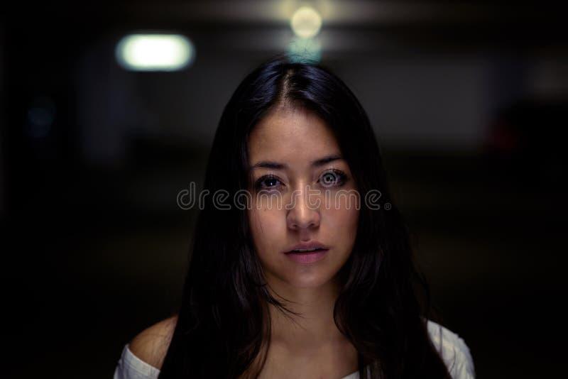 Poważna młoda kobieta przeciw nocy tłu zdjęcia royalty free