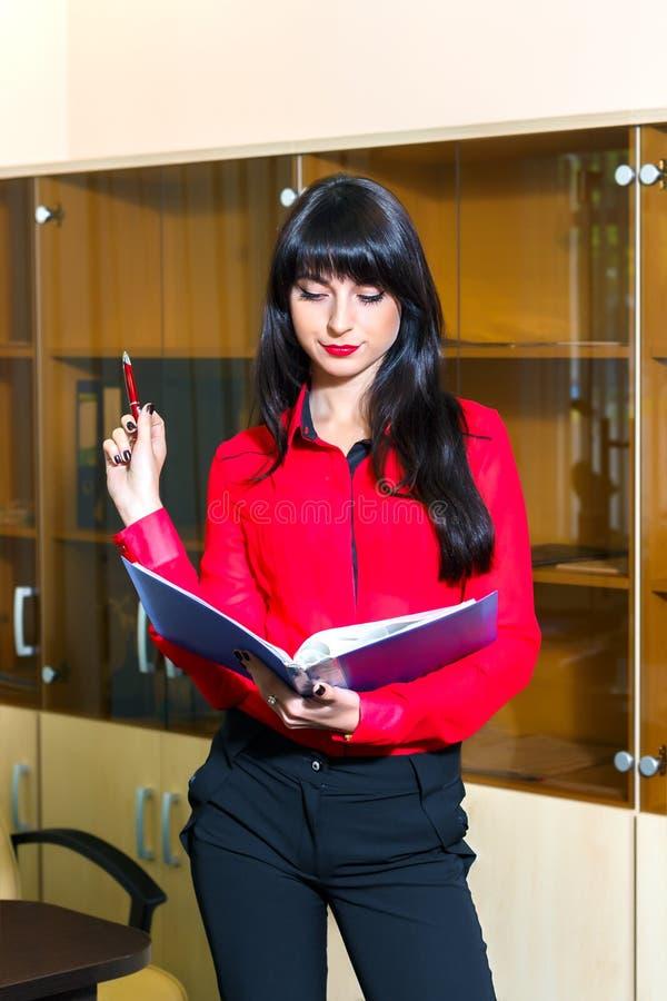 Poważna młoda kobieta w czerwonej bluzce z falcówką dokumenty obraz royalty free